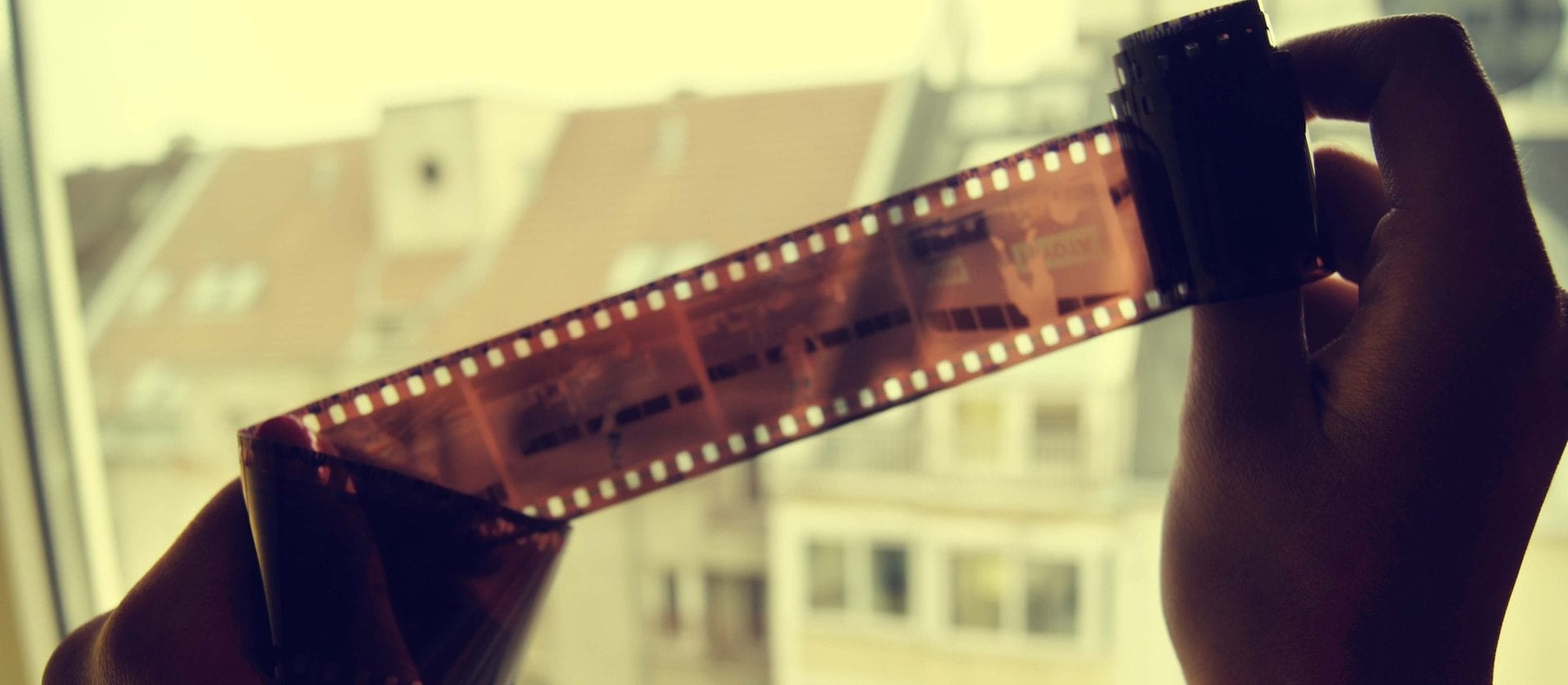 Close up of a film roll being examined near a window. This is apart of our FAQs page.