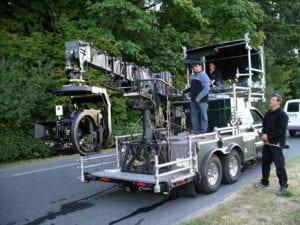 A technocrane on the back of a truck.