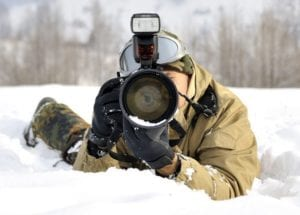 A man shooting in the cold covered in snow.
